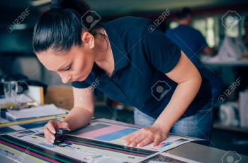 78910109-worker-in-a-printing-and-press-centar-uses-a-magnifying-glass-and-check-the-print-quality